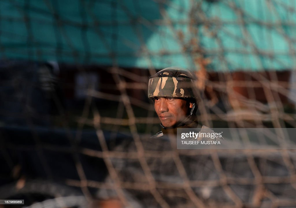 An Indian paramilitary trooper looks from inside a camp in Srinagar on October 3, 2013. Four policemen were injured in a late-night encounter on the outskirts of Srinagar, as suspected militants who were hiding inside a house escaped under the cover of darkness police officials said. AFP PHOTO/Tauseef MUSTAFA