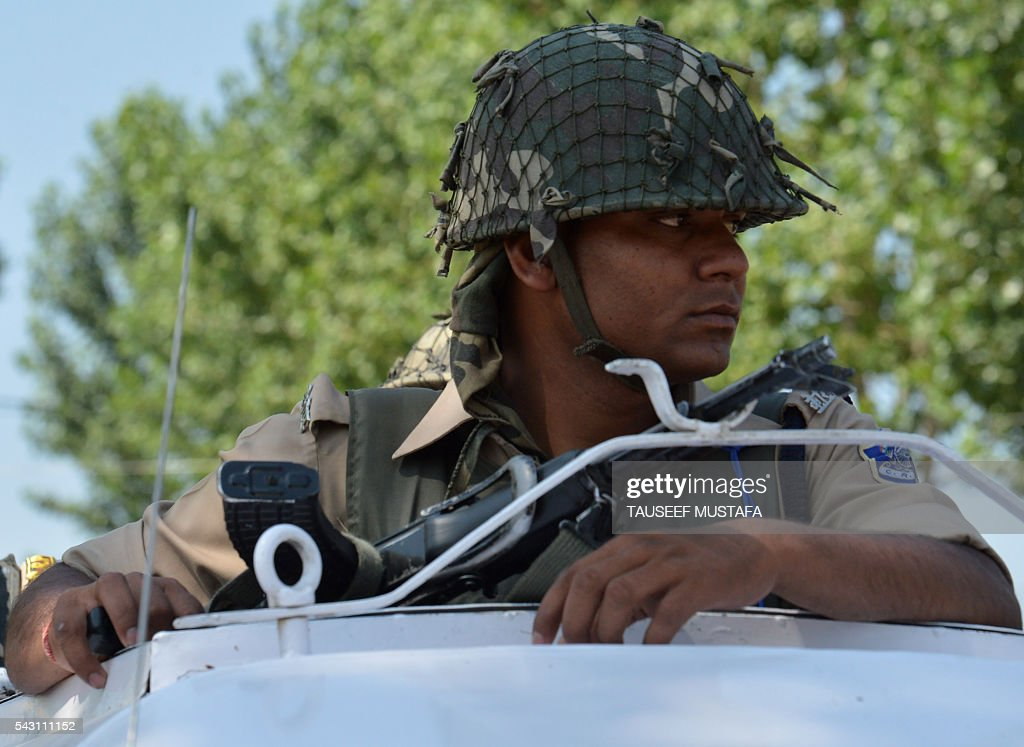 An Indian paramilitary trooper looks on during a wreath laying ceremony for eight colleagues killed in an ambush in Srinagar on June 26, 2016. At least eight Indian paramilitary soldiers and two suspected rebels were killed June 25 near Srinagar in India-administered Kashmir when a group of armed militants ambushed the soldiers' convoy, police said. Four militants sprayed bullets on the convoy carrying members of India's Central Reserve Police Force (CRPF) near Pampore town, killing five soldiers instantly and wounding 20, inspector general of police for the region, Javaid Gillani, told AFP. / AFP / TAUSEEF