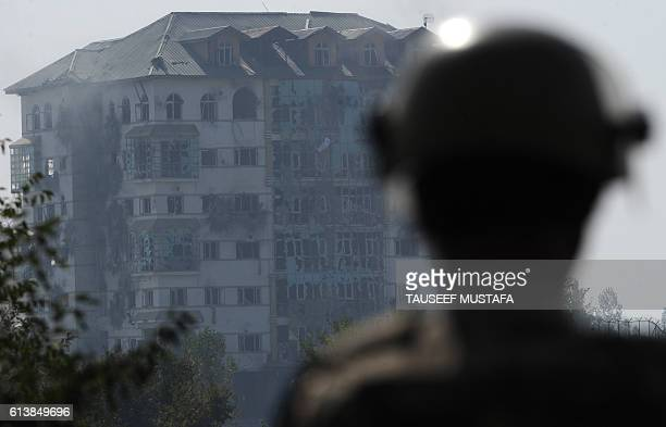 TOPSHOT An Indian paramilitary trooper looks towards a building where suspested militants are thought to be hiding on the second day of a gunfight...