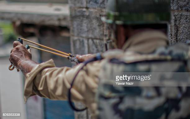An Indian paramilitary trooper shoot stones at Kashmiri Muslim protesters whit his catapult outside Kashmir's grand mosque during an antiIndia...