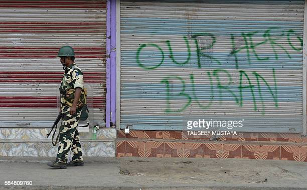 An Indian paramilitary trooper stands guard alongside graffiti bearing the name of popular rebel commander Burhan Wani during a curfew continued...