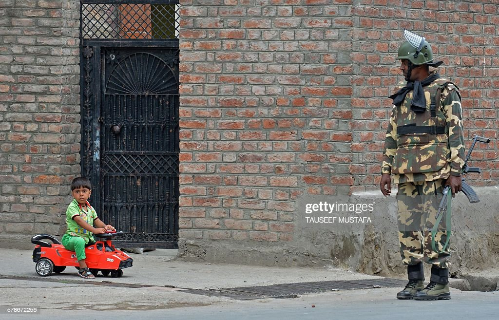 TOPSHOT An Indian paramilitary trooper stands guard as a Kashmiri boy rides a toy car outside his home on the 14th day of a curfew in Srinagar on...