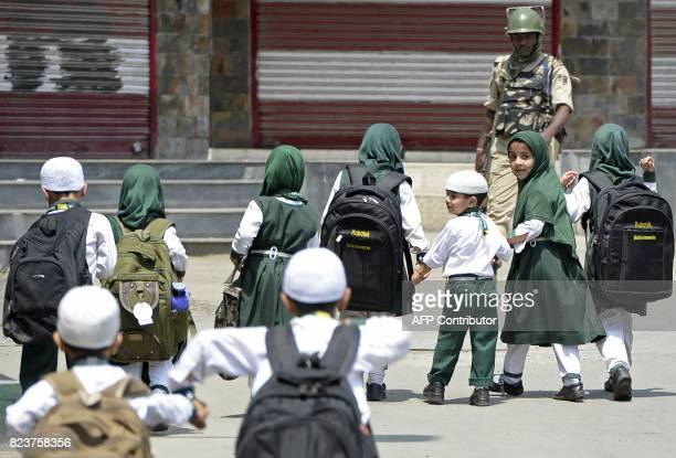 An Indian paramilitary trooper stands guard as a Kashmiri schoolchildren walk past in Srinagar on July 28 2017 Authorities imposed restrictions on...