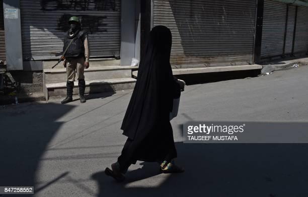 TOPSHOT An Indian paramilitary trooper stands guard as a Kashmiri woman walks near the Jamia Masjid mosque in Srinagar on September 15 2017 The...
