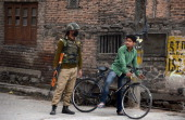 An Indian paramilitary trooper stands guard as a Kashmiri youth cycles past in downtown Srinagar on April 12 2014 as government forces enforce...