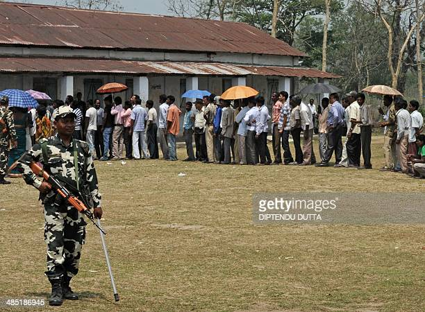 An Indian paramilitary trooper stands guard as residents queue at a polling station in Siliguri on April 17 during national elections India is...