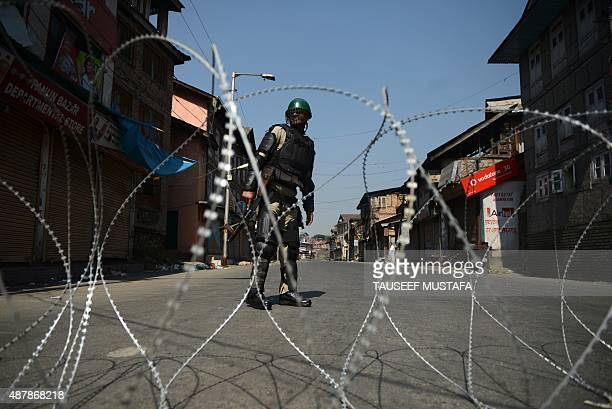 An Indian paramilitary trooper stands guard behind barbed wire during a oneday strike called by separatists in downtown Srinagar on September 12 2015...