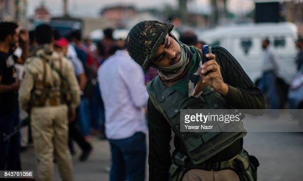An Indian paramilitary trooper take photos with his cell phone near the site after a grenade attack by suspected militants in a busy market on...
