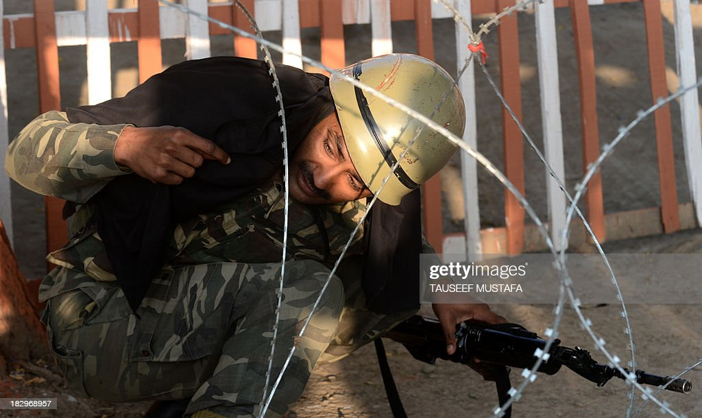 An Indian paramilitary trooper tries to free his bandana which got entangled on a barbed fence wire at the entrance to a camp in Srinagar on October 3, 2013. Four policemen were injured in a late-night encounter on the outskirts of Srinagar, as suspected militants who were hiding inside a house escaped under the cover of darkness police officials said. AFP PHOTO/Tauseef MUSTAFA