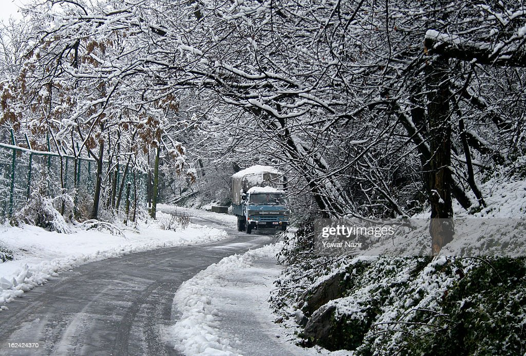 An Indian paramilitary vehicle drives on road amid a snowfall on February 23, 2013 in Srinagar, Indian Administered Kashmir, India. Several parts of the Kashmir Valley, including the summer capital Srinagar, experienced fresh snowfall today, prompting the authorities to issue an avalanche warning and leading to closure of the Jammu-Srinagar Highway, the only road link between Kashmir and rest of India.