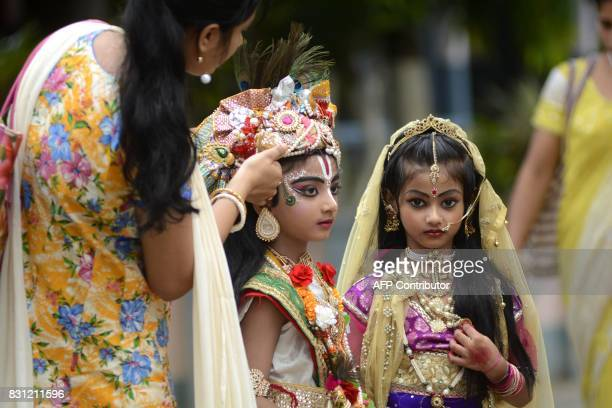 An Indian parent adjusts the costume of her child dressed as Lord Krishna for a competition during Janmashtami celebration at a school in Agartala...
