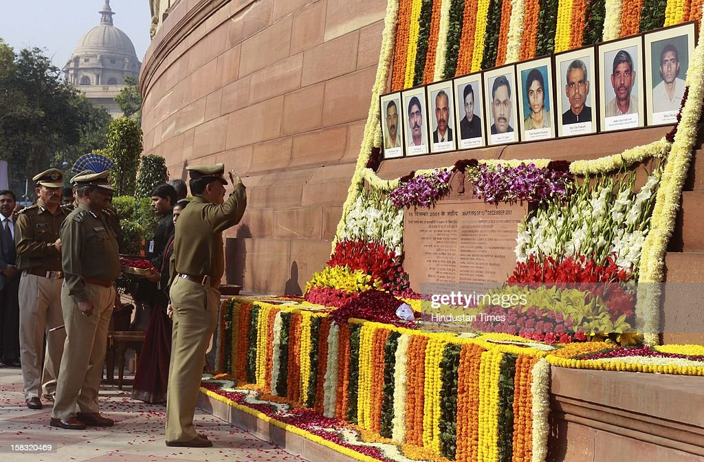 An Indian parliament Security officer pays floral tribute to colleagues who lost their lives in the 2001 attack on India's parliament during an event to mark the 11th anniversary of the attack, on December 13, 2012 in New Delhi, India. 14 persons lost their lives in a terrorist attack on Parliament in 2001.