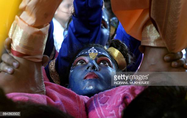 An Indian participant dressed as the Hindu god Lord Krishna helps support others making a 'human pyramid' during a cultural event in the run up to...