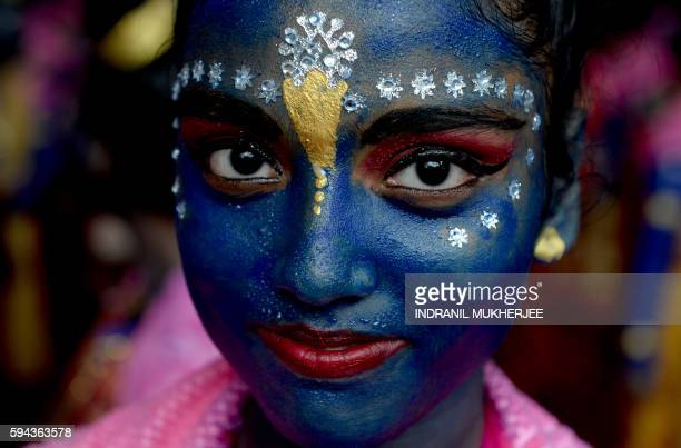 TOPSHOT An Indian participant dressed as the Hindu god Lord Krishna looks on during a cultural event in the run up to the dahi handi celebrations of...