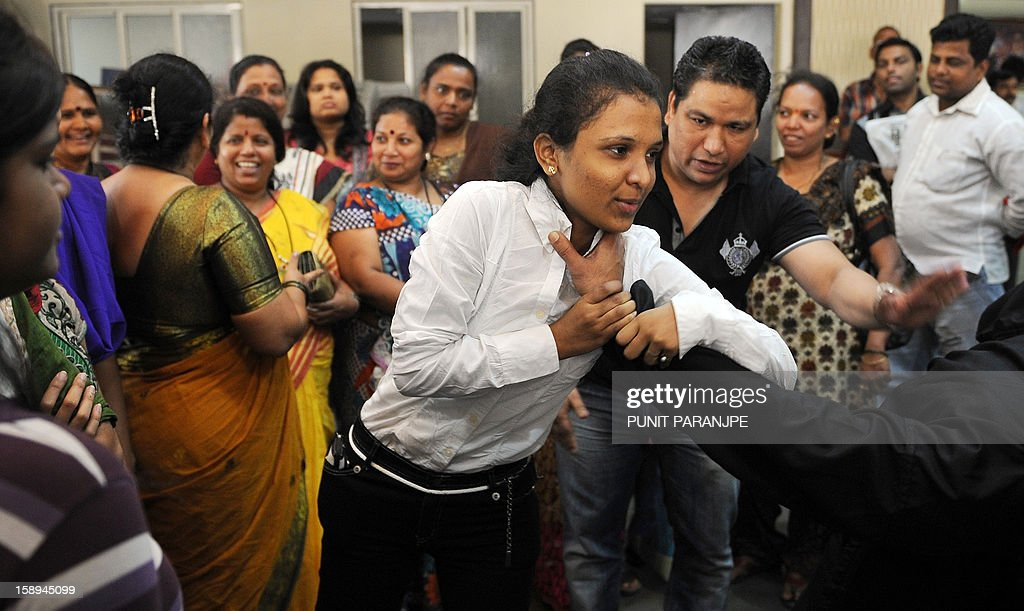 An Indian participant (C) practises a self-defence technique with an instructor during a self-defence classes at a school in Mumbai on January 4, 2013. After nearly three weeks of lurid reporting on a horrifying gang-rape in New Delhi, women in the Indian capital say they are more anxious than ever, leading to a surge in interest in self-defence classes.