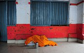 An Indian passenger rests on a platform as he waits for a train at Daraganj railway station in Allahabad on December 22 2014 Dense winter fog has...