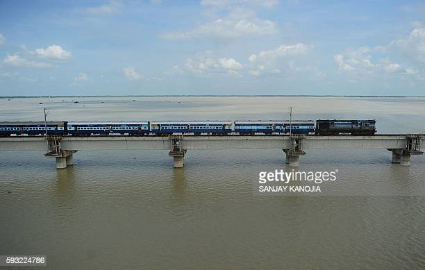TOPSHOT An Indian passenger train crosses a bridge over the flooded river Ganga as water levels in the Ganga and Yamuna rivers rise in Allahabad on...