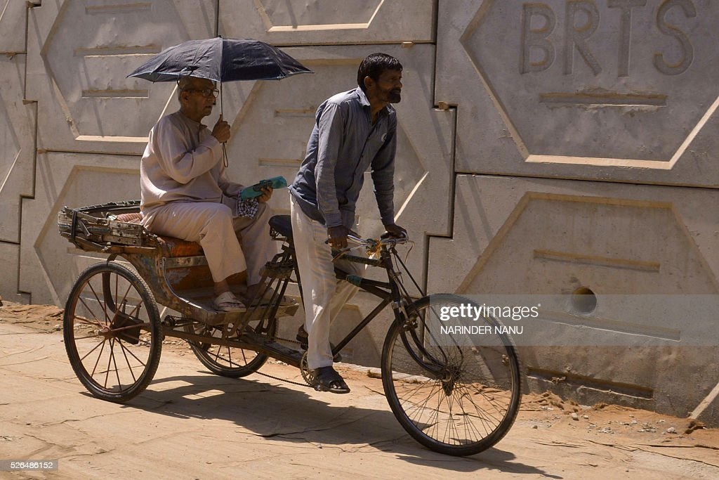 An Indian passenger uses an umbrella to shield himself from the sun as he is transported on a cycle rickshaw during a hot afternoon in Amritsar on April 30, 2016. Hundreds of mainly poor people die at the height of summer annually in India, but temperatures have risen earlier than normal, increasing concerns about this year's overall toll. / AFP / NARINDER