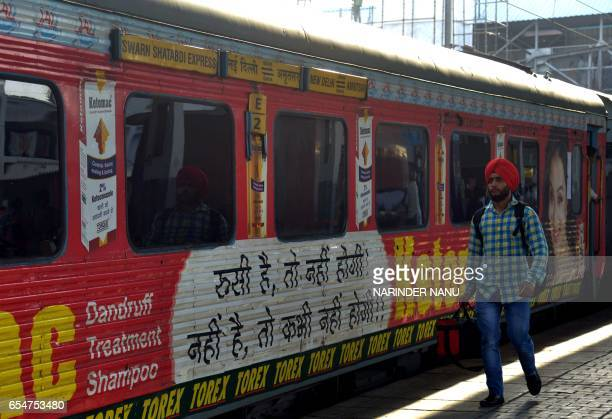 An Indian passenger walks past carriages of The Swarn Shatabdi Express at the railway station in Amritsar on March 18 2017 An Indian farmer's battle...