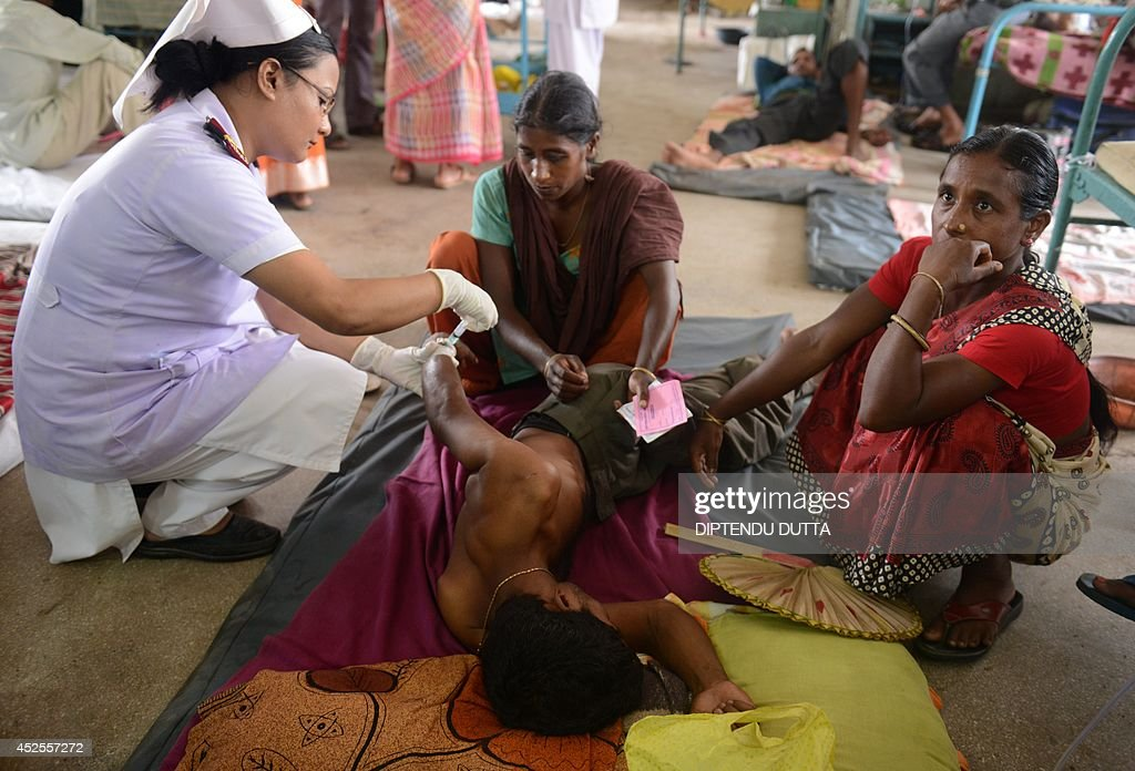 An Indian patient (C) receives an injection while being treated for Japanese encephalitis at the North Bengal Medical College Hospital (NBMCH) on the outskirts of Siliguri on July 23, 2014. Outbreaks of encephalitis in India have killed more than 150 people, with health officials on alert fearing the death toll could rise further, state government directors said. Some 102 people have died in West Bengal state from the mosquito-borne virus which affects mainly malnourished children and can cause brain damage and seizures, said medical education director Sushanta Banerjee. Many of the deaths have occurred since the onset of the monsoon season in June when mosquitoes breed in large numbers. AFP PHOTO/ Diptendu DUTTA