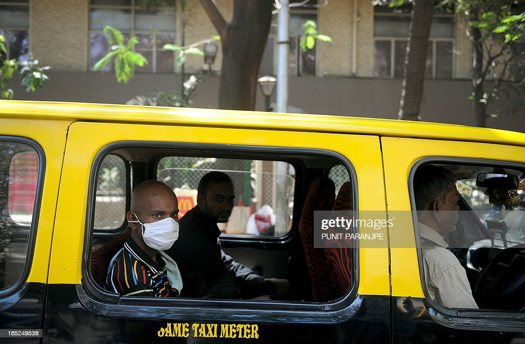 An Indian patient (L, with mask) sits in a cab as he prepares to leave after visiting The Tata Memorial Hospital - specialist cancer treatment and research centre - in Mumbai on April 2, 2013. India's Supreme Court has rejected a patent bid by Swiss drug giant Novartis in a landmark ruling that activists say will protect cheap generic drugs and save lives in developing nations.