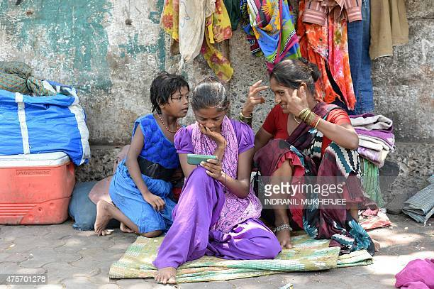 An Indian pavement dweller watches a movie on a mobile phone as others interact in Mumbai on June 3 2015 India recently raised a record 176 billion...
