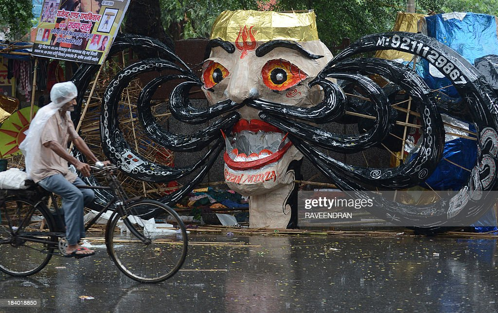 An Indian pedestrian bikes, in heavy rains, past an effigy of the demon king Ravana for sale on the side of the road in New Delhi on October 11, 2013, two days ahead of the Hindu Festival of Dussehra. Dussehra is a Hindu festival that celebrates the victory of good over evil.