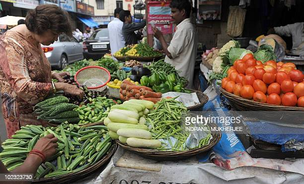 An Indian pedestrian chooses vegetables on display at a street side market in Mumbai on June 14 2010 Indian inflation broke into double figures in...