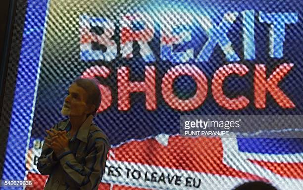 An Indian pedestrian gestures as he stands near a large screen showing news of Britain's vote to exit the European Union in Mumbai on June 24 2016...