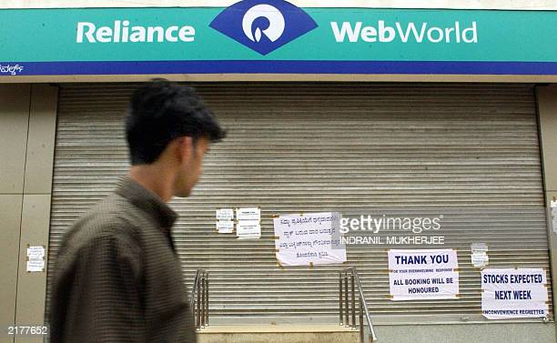 An Indian pedestrian glances at posters pasted on the closed shutters of a Reliance Infocom mobile phone outlet in Bangalore 04 July 2003 Almost all...