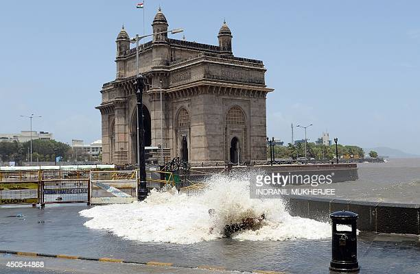 An Indian pedestrian is covered with water as waves come ashore during high tide near the Gateway of India in Mumbai on June 13 2014 The Indian...