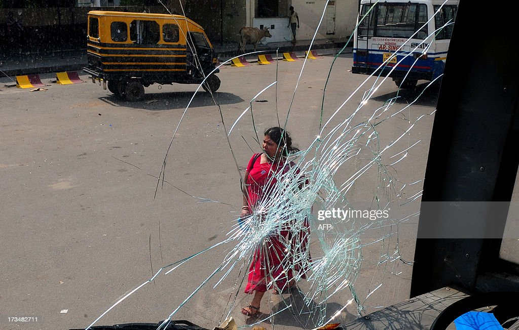 An Indian pedestrian is seen through the smashed window of a bus damaged during a protest against reservation for Other Backward Classes (OCC) candidates in the Uttar Pradesh Public Service Commission, in Allahabad on July 15, 2013.