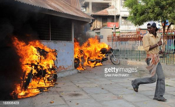 An Indian pedestrian looks back after sliding down the roof of a police station amid burning motorbikes during a protest against an antiIslam film in...
