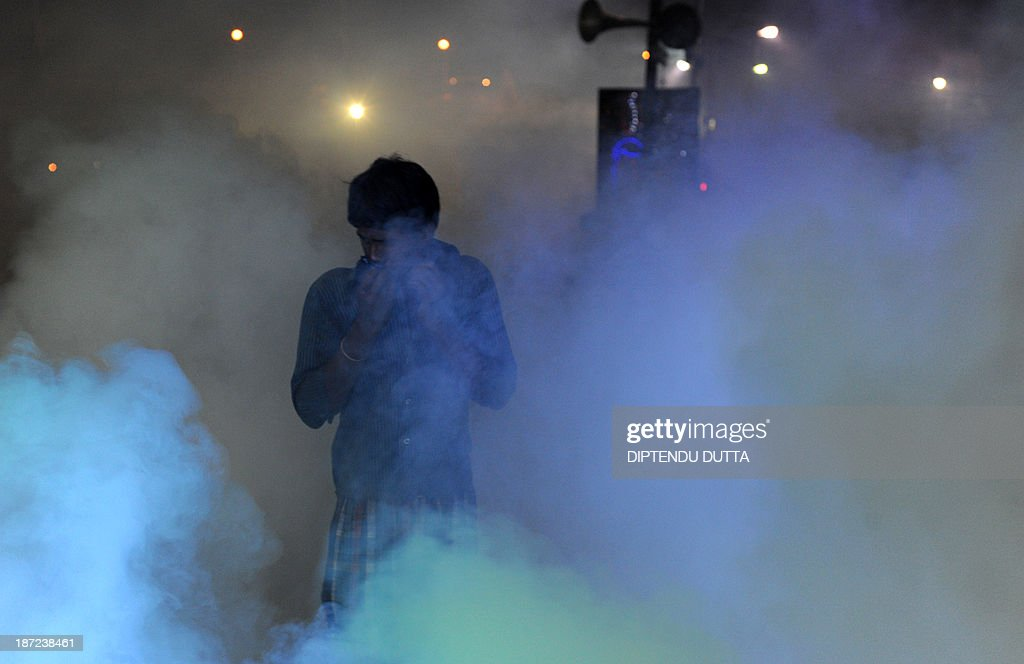 An Indian pedestrian protects his face as he is engulfed in a cloud of pesticide during a dengue prevention drive at a slum area to prevent mosquitos from breeding in Siliguri on November 7, 2013. Dengue fever is a mosquito-borne disease with no known cure or vaccination that arrives across the sub-continent with the monsoon rains , just as the scorching heat of the summer is subsiding. AFP PHOTO/Diptendu DUTTA