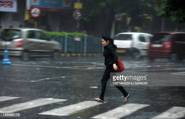 An Indian pedestrian runs across a road as she seeks shelter from a sudden downpour in Kolkata on October 4 2012 Rain and thundershowers which struck...