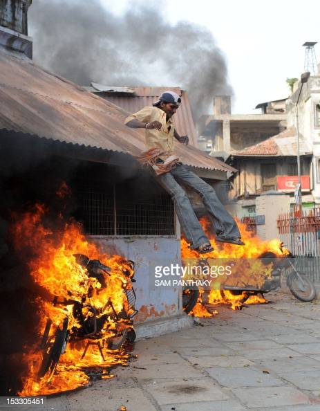 An Indian pedestrian slides down the roof of a police station amid burning motorbikes during a protest against an antiIslam film in Ahmedabad on...