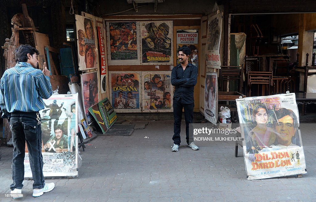 An Indian pedestrian (L) speaks with the vendor at A-1 Corner Bollywood memorabilia shop in Mumbai on April 30, 2013. One hundred years after the screening of a black-and-white silent film, India's brash, song-and-dance-laden Bollywood film industry celebrates its centenary later this week. The milestone will be marked with little fanfare, while India will be honoured as 'guest country' at next month's Cannes festival.