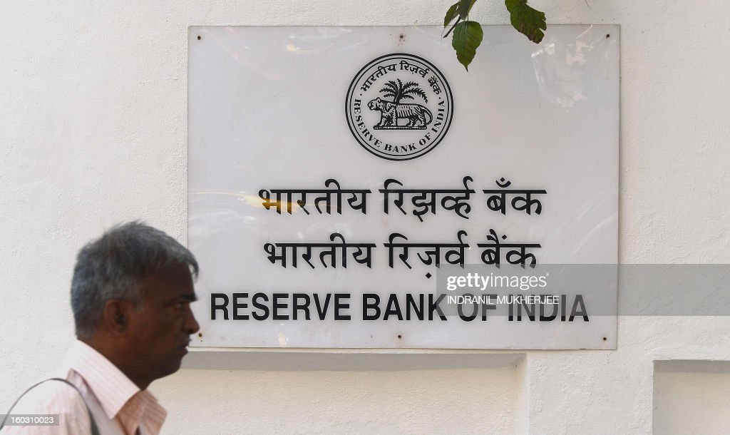 An Indian pedestrian walks past a sign outside the Reserve Bank of India headquarters in Mumbai on January 29 2013 India's central bank cut its main...