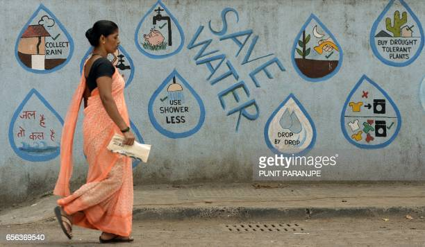 TOPSHOT An Indian pedestrian walks past a wall adorned with water conservation messages in Mumbai on March 22 on World Water Day Recycling the...