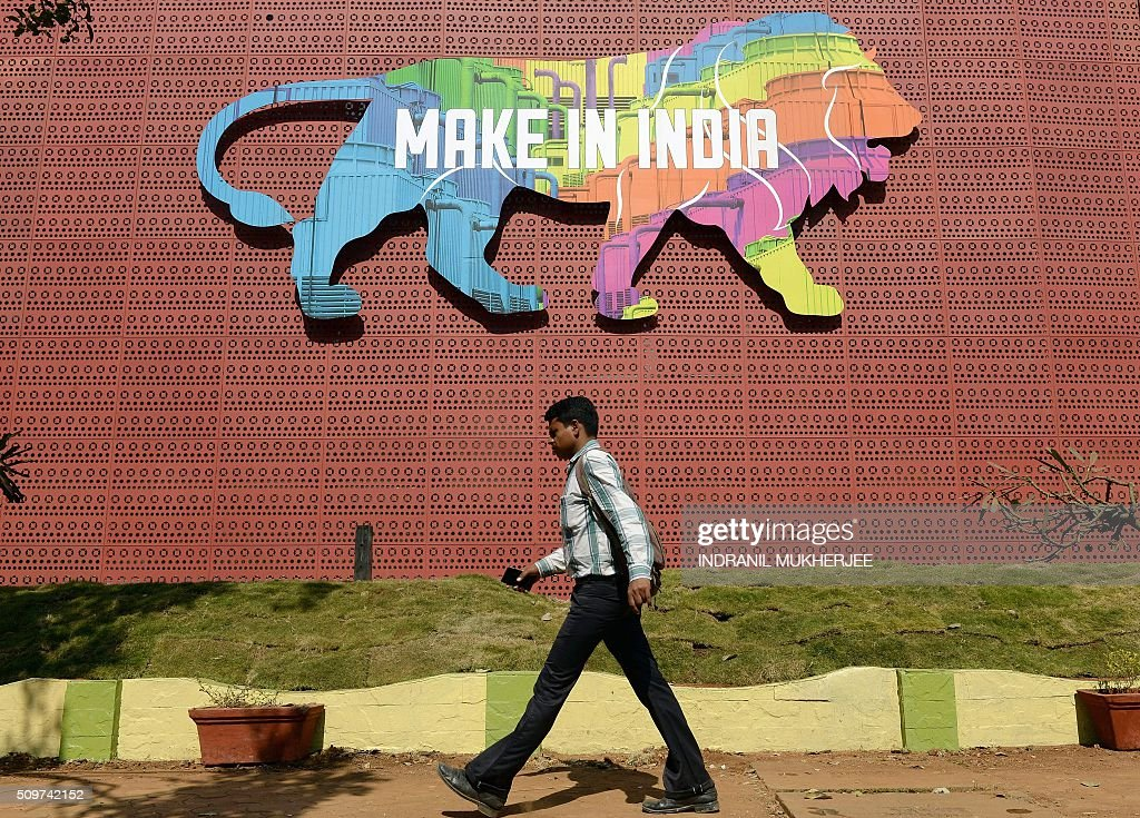 An Indian pedestrian walks past a wall bearing the image of the mascot for the 'Make in India Week' at the venue in Mumbai on February 12, 2016. Over 190 companies, and 5,000 delegates from 60 countries, are due to take part in the first 'Make in India' week to be held in Mumbai from February 13-18. AFP PHOTO / INDRANIL MUKHERJEE / AFP / INDRANIL MUKHERJEE
