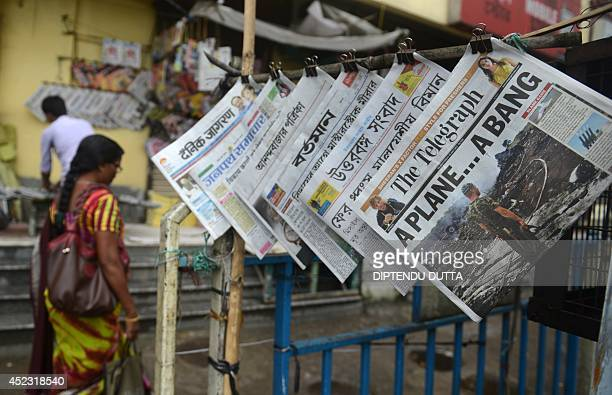 An Indian pedestrian walks past newspapers featuring the crash of a Malaysia Airlines plane carrying 298 people from Amsterdam to Kuala Lumpur at a...