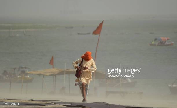 TOPSHOT An Indian pedestrian walks through a dust storm at the Sangam the confluence of the rivers Ganges Yamuna and mythical Saraswati in Allahabad...