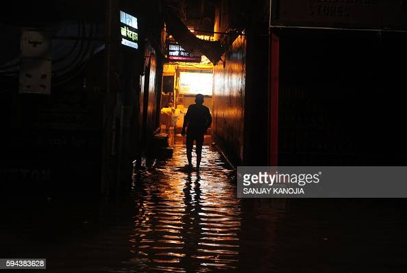 An Indian pedestrian walks through a flooded street at Dashashwamedh Ghat in Varanasi on August 23 2016 India's holy city of Varanasi has been forced...