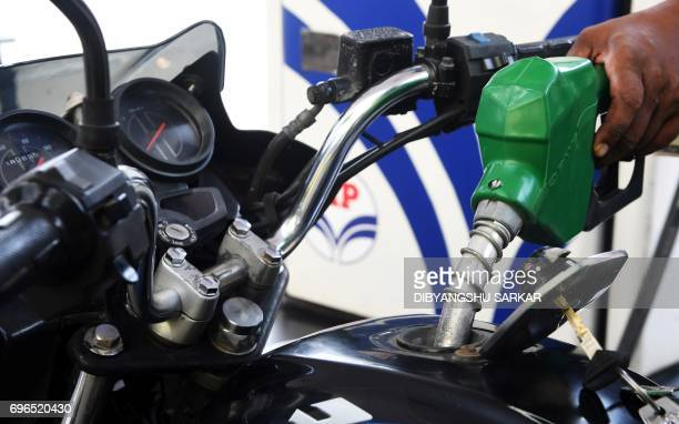 An Indian petrol pump attendant serves a customer at a gas station in Kolkata on June 16 2017 India is to begin revising national petrol and diesel...