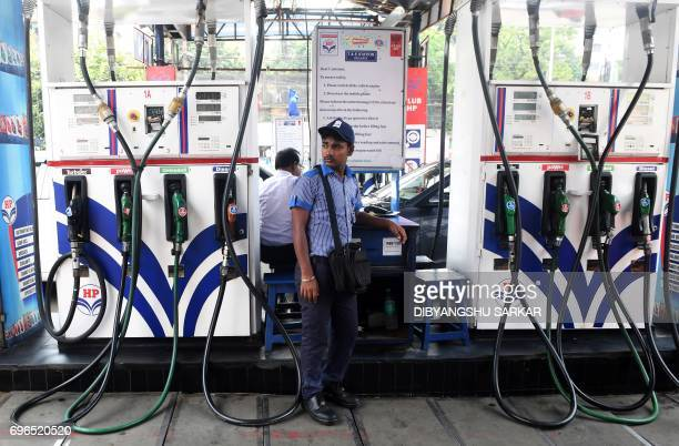 An Indian petrol pump attendant waits for customers at a gas station in Kolkata on June 16 2017 India is to begin revising national petrol and diesel...