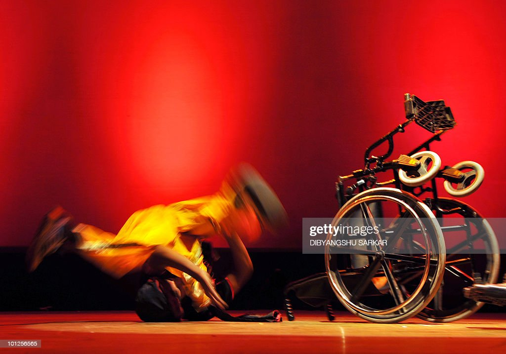 An Indian physically challenged artists performing yoga falls of his wheelchair during a function in Bangalore on May 28, 2010. NGO Abilities Unlimited works with artists who suffer conditions such as polio, dyslexia, cerebral palsy and autism and is the first professional dance�theater troupe in India to educate and employ people with disabilities through choreographed works and public performances that integrate the arts with career opportunities and training. AFP PHOTO/Dibyangshu Sarkar