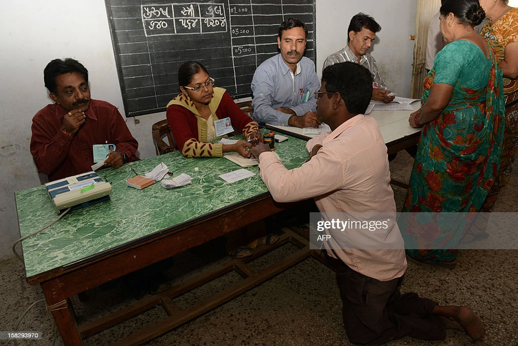 An Indian physically challenged voter registers with officials as he arrives to cast his vote in state assembly elections at Sanand some 30kms. from Ahmedabad on December 13, 2012. The first phase of voting in state assembly elections in the western Indian state of Gujarat has begun with the next phase on December 17, 2012. AFP PHOTO/Sam PANTHAKY