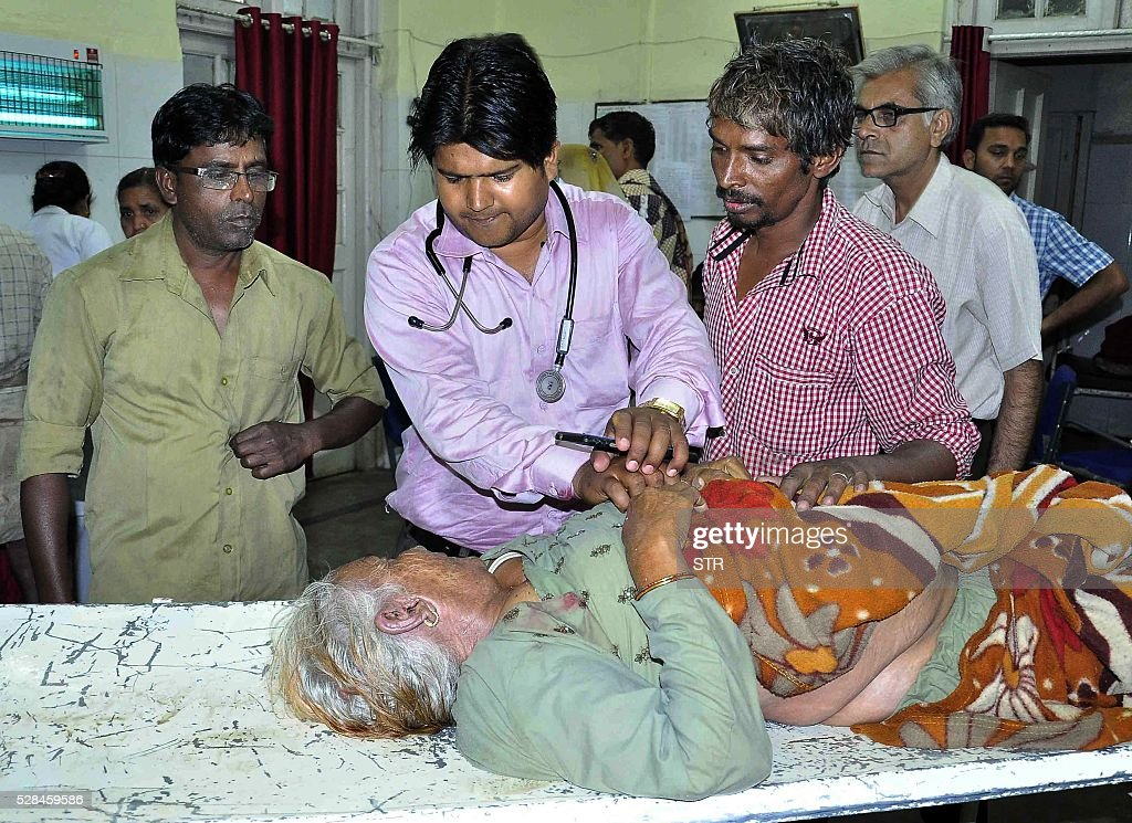 An Indian pilgrim injured after a tent collapse caused a stampede at a religious event is treated by medical staff at a hopsital in Ujjain on May 5, 2016. At least seven pilgrims were killed after a storm caused a tent to collapse onto devotees at the Kumbh Mela mass religious gathering in central India, triggering a small stampede, police said May 5. Forty others were injured when the makeshift tent caved in following strong winds at one of the sites of the Kumbh, a pilgrimage that draws millions over four weeks to participate in a sacred bathing ritual. / AFP / STR
