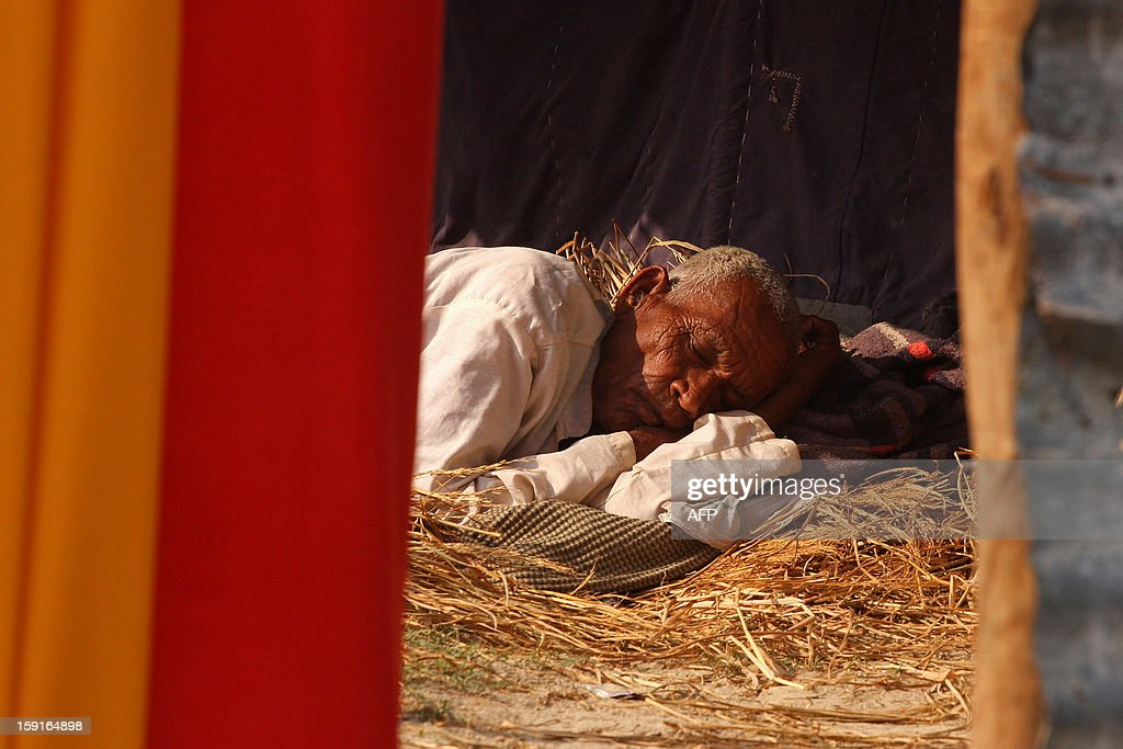 An Indian pilgrim rests over a bed of hay on a sunny day following last week's cold spell across the region, ahead of the Kumbh Mela in Allahabad on January 9, 2013. The Kumbh Mela, which is scheduled to take place in the northern Indian city in January and February 2013, is the world's largest gathering of people for a religious purpose and millions of people gather for this auspicious occasion. AFP PHOTO/Sanjay KANOJIA