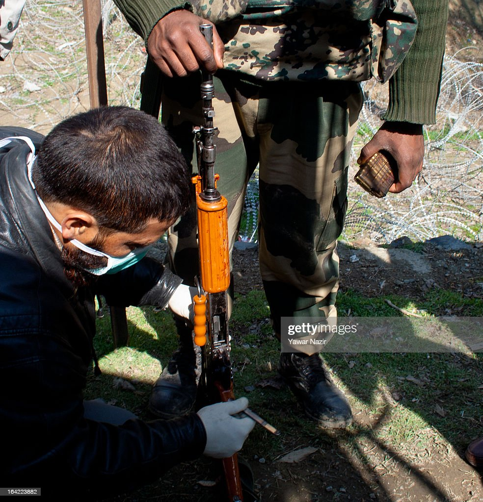 An Indian police man takes blood samples from a rifle of a killed paramilitary soldier after an attack by suspected militants this early morning on March 21, 2012 in Srinagar the summer capital of Indian administered Kashmir, India. One Indian Border Security Force (BSF) soldier was killed and two others wounded when suspected militants attacked their vehicle on a highway in the outskirts of Srinagar. The attack is the second in the last ten days after a suicide attack by militants left five Indian paramilitary soldiers dead in one of the deadliest attack's in the last five years. The Kashmir valley is on alert since the hanging of Afzal Guru, a local who was convicted of carrying out a deadly attack on the Indian Parliament attack in 2001.